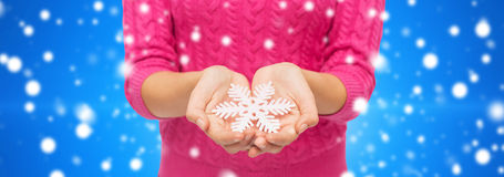 Close up of woman in sweater holding snowflake Stock Images