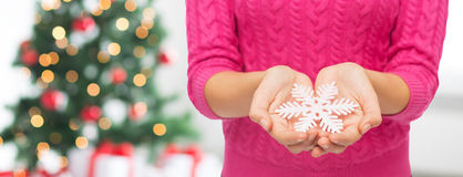 Close up of woman in sweater holding snowflake Stock Photos