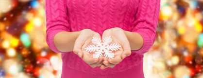 Close up of woman in sweater holding snowflake Stock Photography