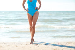 Close up of woman in swimsuit walking on beach Stock Photo