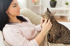 Close up of woman with tabby cat in bed at home. Pets, hygge and people concept - close up of woman with tabby cat in bed at home stock images