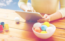Close up of woman with tablet pc and easter eggs Royalty Free Stock Photos