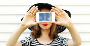 Close-up woman taking selfie picture by phone on white wall. Background stock photos