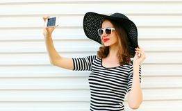Close-up woman taking selfie picture by phone on white wall. Background royalty free stock photography