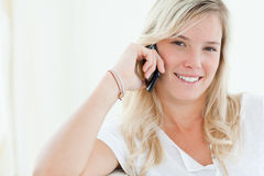 Close up of a woman talking on her phone. In her house Stock Images
