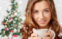 Close up of woman with tea cup over christmas tree Stock Image