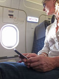 Close up of woman text messaging on cell phone in airplane Stock Image