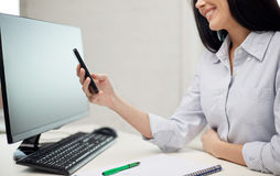 Close up of woman texting on smartphone at office Royalty Free Stock Photo