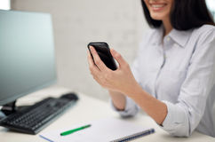Close up of woman texting on smartphone at office Royalty Free Stock Photos