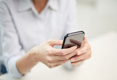 Close up of woman texting on smartphone at office Royalty Free Stock Images