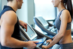 Close up of woman with trainer on treadmill in gym Stock Image