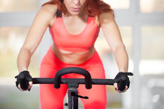 Close-up, woman training on cycling machine in fitness center Royalty Free Stock Images