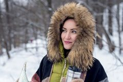 Close-up of a woman traveling in winter clothes standing in the winter forest with a map foggy in the morning. Wanderlust. copy sp. Ace Royalty Free Stock Photography