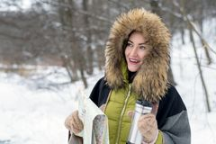Close-up of a woman traveling in winter clothes standing in the winter forest with a map foggy in the morning. Wanderlust. copy sp. Ace Stock Image