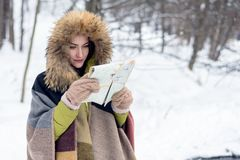 Close-up of a woman traveling in winter clothes standing in the winter forest with a map foggy in the morning. Wanderlust. copy sp. Ace Stock Photos