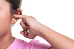 Close up woman trying cleaning her ear by using her finger isolated on white stock image