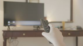 Woman with TV Remote in hand changing channels. Close up of woman with TV Remote in hand changing channels stock video