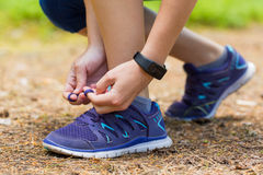 Close up of woman tying shoe laces in summer workout. royalty free stock photography