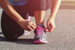 Woman tying sports her shoe. Prepare for run in the park stock photos