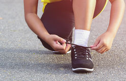 Woman tying sports her shoe. Prepare for run in the park stock image
