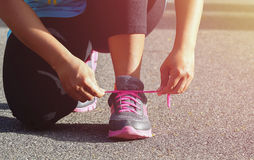 Woman tying sports her shoe. Prepare for run in the park royalty free stock photo