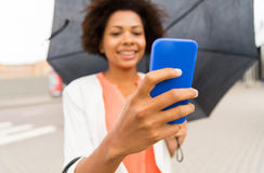Close up of woman with umbrella and smartphone Stock Image