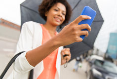 Close up of woman with umbrella and smartphone Stock Images