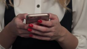 Close-up, woman uses a mobile phone, dials a text message on the social network. Close-up, a woman with red nails and manicure uses a mobile phone, dials a text stock video