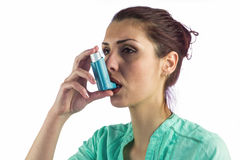 Close-up of woman using asthma inhaler. Against white background Royalty Free Stock Images