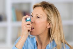Close-up woman using asthma inhaler in living-room. Close-up of woman using the asthma inhaler in her living-room stock image