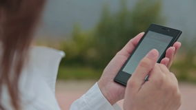 Close up of a woman using mobile smart phone. Outdoor stock video footage