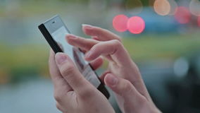 Close up of a woman using mobile smart phone. Outdoor stock footage