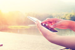 Close up of a woman using mobile smart phone at park outdoor, Royalty Free Stock Photography