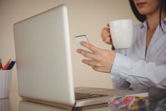 Close up of woman using smart phone while sitting by laptop. At home Stock Image