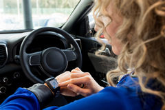 Close up of woman using smart watch in car. During test drive Royalty Free Stock Photo