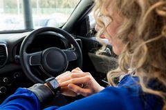 Close up of woman using smart watch in car. During test drive Stock Photography