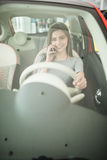 Close up of woman using smartphone while driving car stock photography