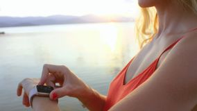 Close-up of woman using smartwatch and touching touchscreen. Young blonde woman using smartwatch app on beach stock footage