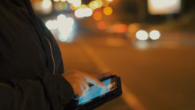 Close-up of woman using tablet pc outdoors in the city at night, only hands to be seen. stock footage