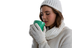 Close up of woman in warm clothing having coffee. While standing against white background Stock Photography