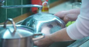Woman washing dishes in sink in kitchen