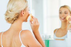 Close up of woman washing face with sponge at home Royalty Free Stock Photos
