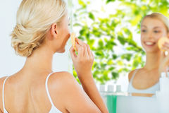 Close up of woman washing face with sponge at home Royalty Free Stock Images