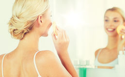 Close up of woman washing face with sponge at home Royalty Free Stock Photography
