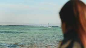Close-up woman watching a man ride a windsurf, woman look in to horizon beautiful sea view and blue sky, full hd