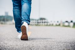 Close up woman wear jean and white sneaker walking forward on hi. Ghway road in sunny day,Alone travel or solo traveler concept Royalty Free Stock Photos