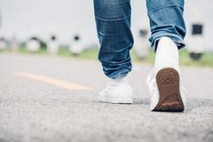 Close up woman wear jean and white sneaker walking forward on hi. Ghway road in sunny day,Alone travel or solo traveler concept Royalty Free Stock Image