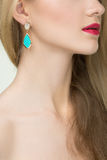 Close up of woman wearing shiny diamond earrings Royalty Free Stock Image