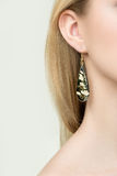 Close up of woman wearing shiny diamond earrings Royalty Free Stock Images