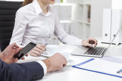 Close up of woman in white blouse and her coworker in office Stock Image